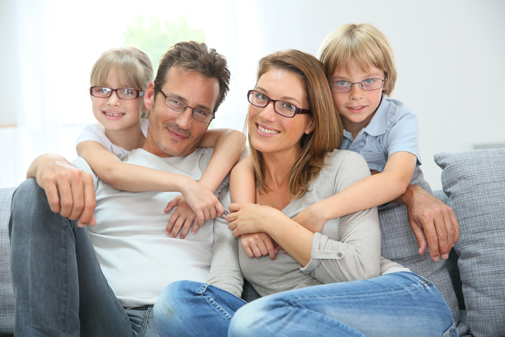 a family of four smiling and wearing glasses